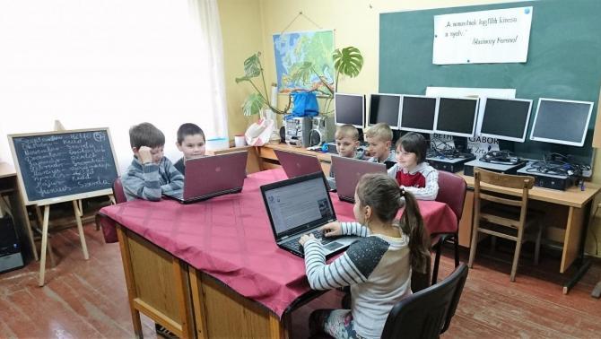 A rahói magyar iskolások az ajándékba kapott laptopokkal, háttérben az asztali gépek